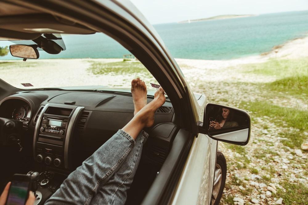 vrouw benen op auto dashboard zee op achtergrond.