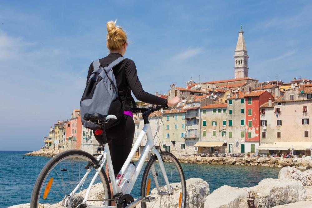Jonge actieve vrouwelijke toerist fietsen en genieten van prachtig uitzicht van Rovinj, Istrië, Kroatië.
